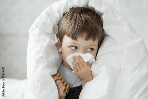 Fotografia, Obraz  boy wipes his nose with a tissue