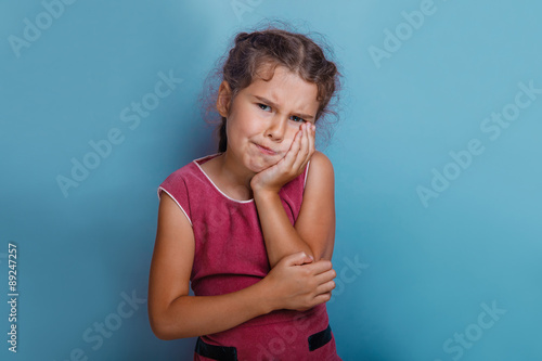 Fotografia  Girl European  appearance decade toothache on a blue background