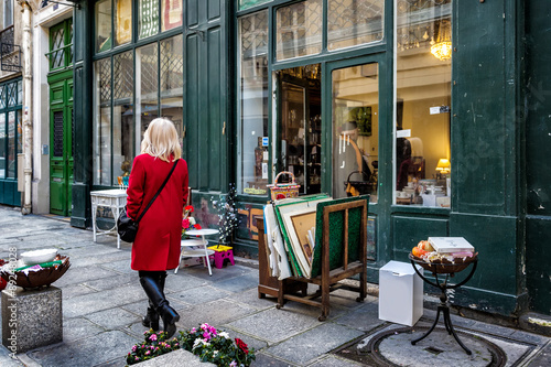 Obraz na plátne Paris street antique shop sidewalk shopper in red coat