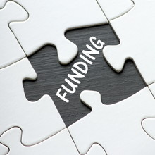 The Word Funding In White Text On A Blackboard As Revealed By A Missing Jigsaw Puzzle Piece