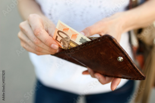 Fotografía  Girl is taking out money from wallet
