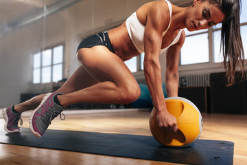 Fototapeta na wymiar Muscular woman doing intense core workout in gym