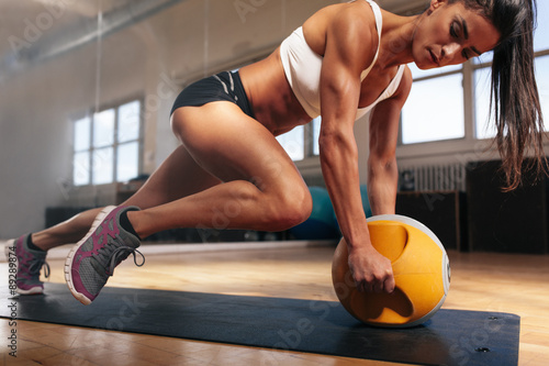 Fotografiet  Muscular woman doing intense core workout in gym