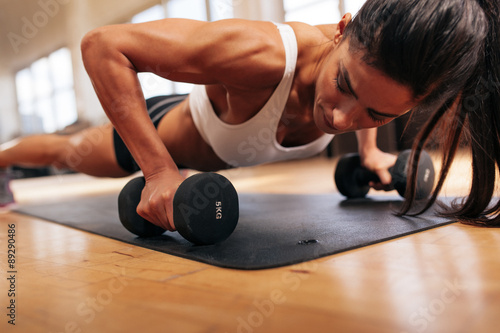 Fotografiet  Strong young woman doing push ups