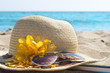 Straw hat, sunglasses and a book on the beach. Summer vacation a