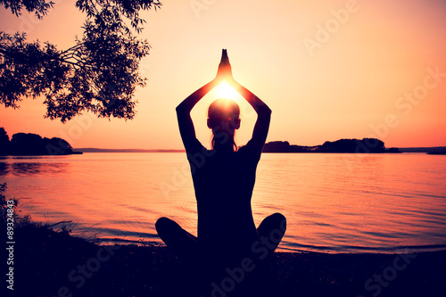 Juliste  Silhouette woman practicing yoga posing on beach at sunset
