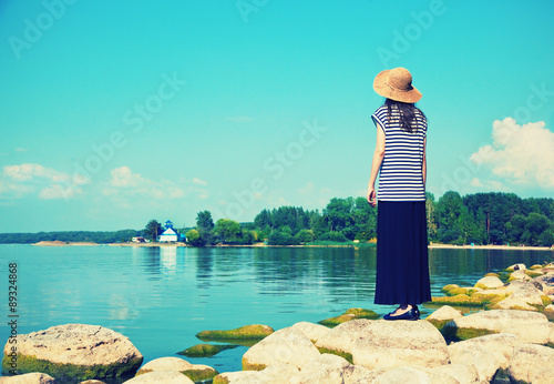 Poster Turquoise woman standing alone at sea coast and looking at water