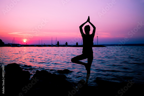 Fotobehang Draw Silhouette woman practicing yoga posing on beach at sunset