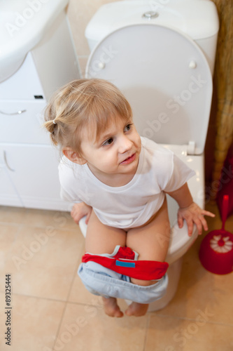 Cute Little Girl Sitting On Toilet Lagerfoto 340508207