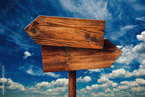 Blank Rustic Opposite Direction Wooden Sign Against Clouds Poster