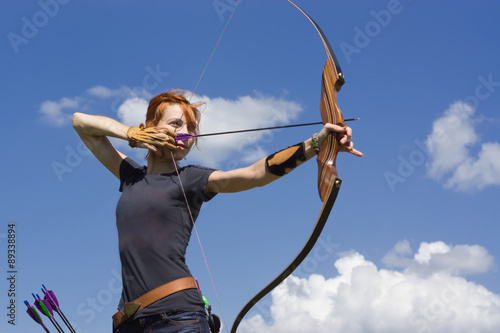 Vászonkép Archery woman bends bow archer target narrow