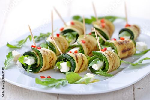 Foto auf AluDibond Bar Gebratene Zucchiniröllchen mit Feta und Rucola, mit Olivenöl und Paprika serviert
