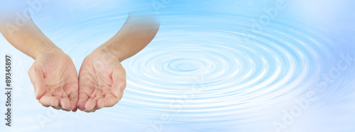 Valokuva  Water Healing Therapist - Female open cupped hands on a pale blue water ripple e