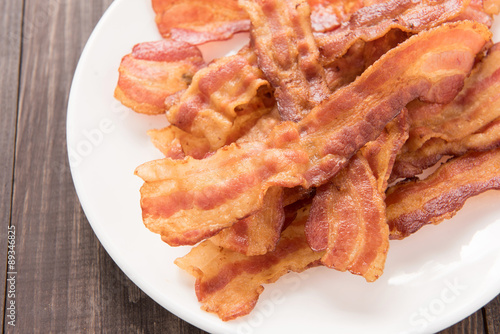 Fotografie, Obraz  Closeup of fried bacon strips on white plate