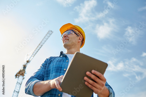 Fotografía  builder in hardhat with tablet pc at construction