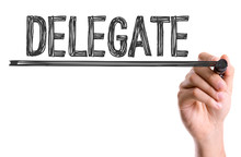 Hand With Marker Writing The Word Delegate