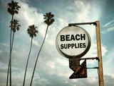 Fototapeta Młodzieżowe - aged and worn vintage photo of beach supplies sign