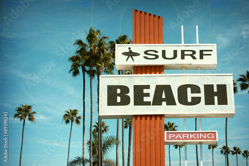 Photo  aged and worn vintage photo of surf beach sign with palm trees