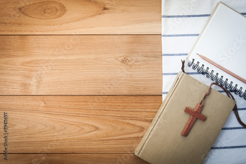 Fotografie, Obraz  wooden Christian cross necklace on holy Bible on wood table