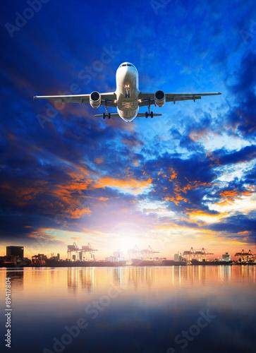 Naklejka premium ładunek lotniczy samolot lecący nad statkiem w porcie portowym do przewozu towarów