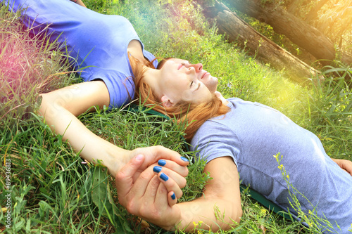 Fotografie, Obraz  young couple in love, hand in hand, lying on the green grass in a park closing eyes and dreaming