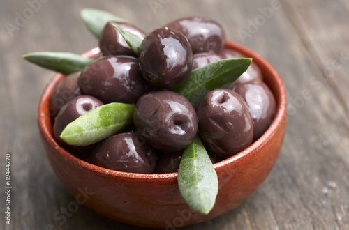 Fényképezés  Black olives with leaves in bowl