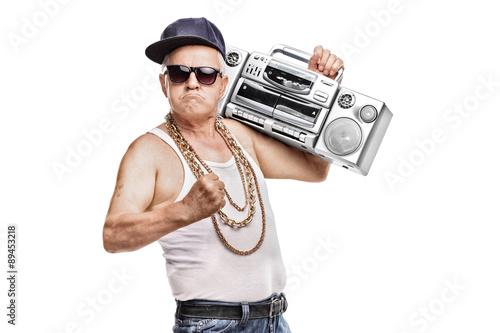 Fototapeta Mature man in hip-hop outfit holding a ghetto blaster obraz
