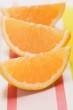 Three orange wedges on striped fabric background