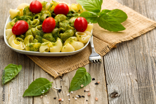 Poster  Traditional basil pesto dish with cherry tomatoes on rustic wood