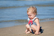 Portrait of crying girl in swimsuit on beach
