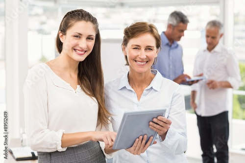 Fototapety, obrazy: Smiling businesswomen using tablet in a meeting
