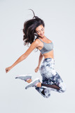 Full length portrait of smiling sports woman jumping - 89531471