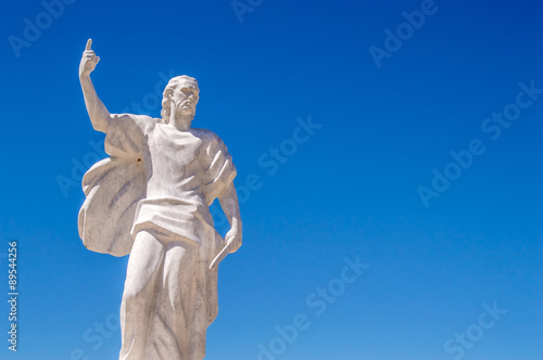 A statue of St Elijah the prophet holding a knife on a blue sky Wallpaper Mural