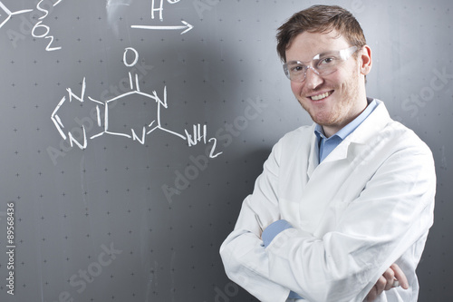 Germany,Portrait of young scientist standing next to chemical equation on chalk board,smiling