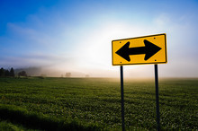 Directional Road Sign In Front Of A Corn Field.