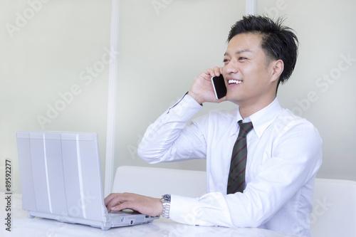 Fotografía  パソコンしながら電話する男性