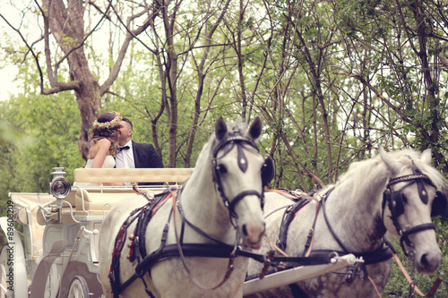 Fotografía  Bride and groom sitting in a white carriage