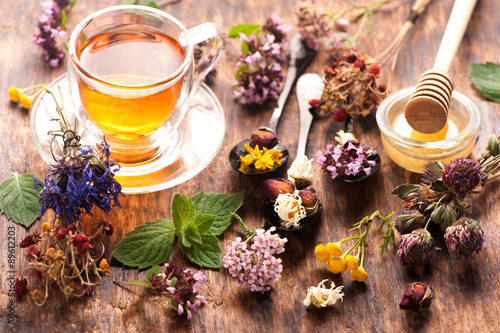Obraz na plátně Cup of herbal tea with wild flowers and various herbs