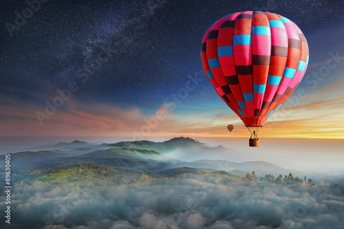 Poster Ballon Colorful hot-air balloons flying over the mountain with with stars. Beautiful mountains landscape with clouds at sunset