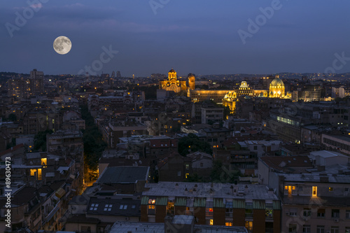 Foto op Aluminium Volle maan Night panorama of Belgrade with National Assembly and St Mark church