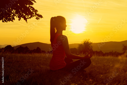 Foto op Aluminium Ontspanning Young athletic woman practicing yoga on a meadow at sunset, silhouette
