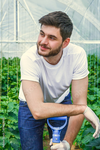 Photo  Young  sitting between rows of plants, working in a greenhouse.