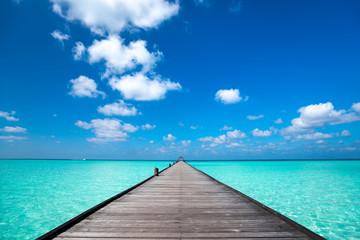 Drewniane molo z niebieskim tle morza i nieba