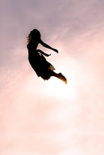 Silhouette Of Woman Falling Through Sky