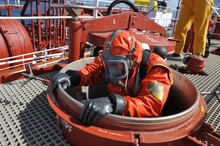 Man In Chemical Suit Entering Inside Cargo Tank On Deck Of Chemical Tanker For Cleaning Operation