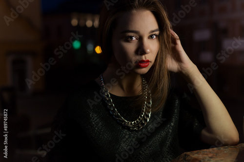 beautiful sexy girl with big lips with red lipstick on a city street at night near the lantern