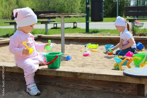 Fotografie, Obraz  Two adorable little girls playing with molds and scoops in a sandbox on the play