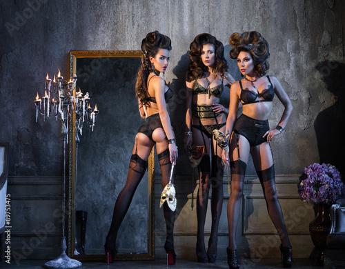 Three girls in lingerie, masks, standing near a vintage mirror
