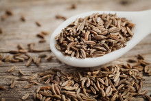 Cumin Seeds Or Caraway In White Spoon On Wooden Board