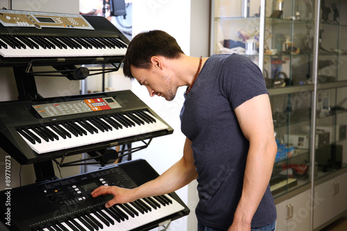 Poster de jardin Magasin de musique Handsome young man in music store